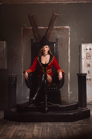 Beautiful woman trainer in a circus suit and a hat sits on the throne photo