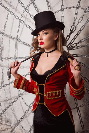 Beautiful woman trainer in a circus suit and a hat. photo