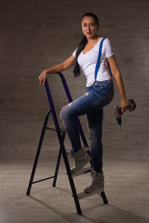 leans on hand: An adult woman dressed in jeans, a white T-shirt leans on a stepladder with a drill in her hand
