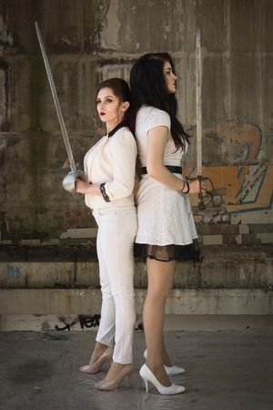 Duel. Two pretty women with swords ready to fight. Stock Photo