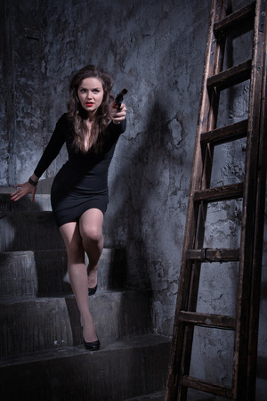indication: Noir film style woman in a black suit posing with a gun