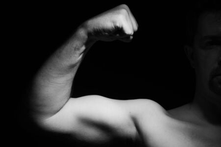 Muscular man showing his muscles. Black and white