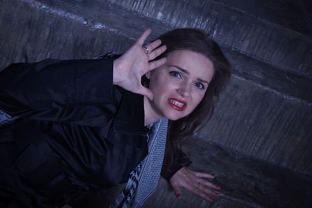outraged: Frightened woman with scarf in horror. Noir film style