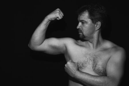 Muscular man showing his muscles. Black and white photo