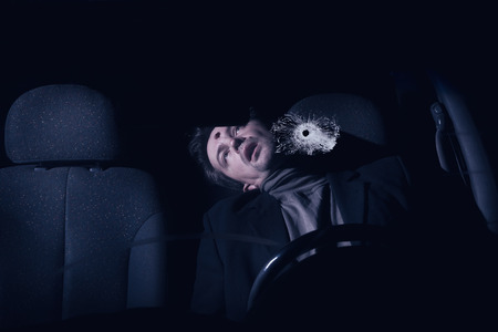 Businessman killed in the car. Crime scene imitation photo