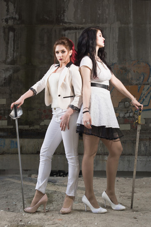 rival: Duel. Two pretty women with swords ready to fight. Stock Photo