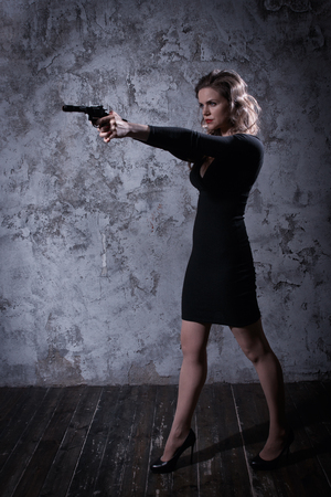 casualty: Noir film style woman in a black suit posing with a gun