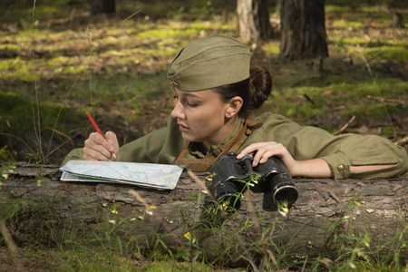 Woman in uniform of the Red Army of the Second World War holding a binoculars and writing.