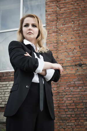 Noir film style woman in a black suit posing in a street