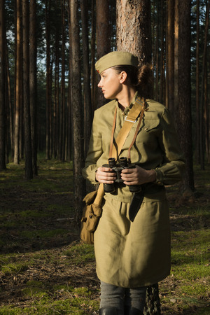 Woman in uniform of the Red Army of the Second World War. She watches through binoculars and scouts.