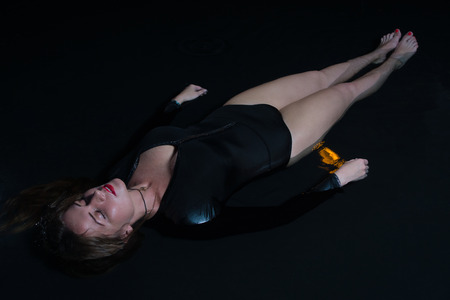 Young woman lying in a water in a poetic representation. Stock Photo