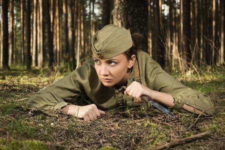 Wirl en uniforme de l'armée rouge de la seconde guerre mondiale. Elle rampe sur le sol avec un couteau à la main