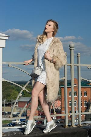 Fashionable girl walking on a city landscape