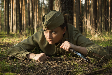 Wirl in uniform of the Red Army of the Second World War. She crawls on the ground with a knife in her hand