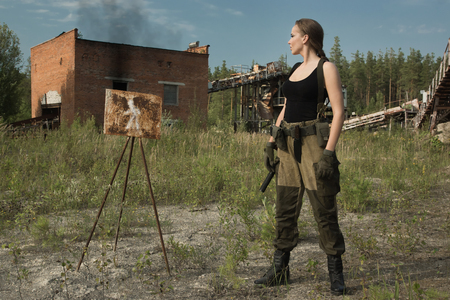 Girl in uniform with a gun in an abandoned factory Stock Photo