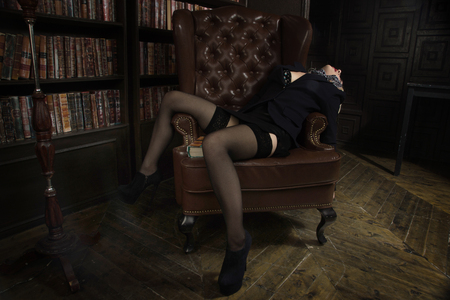 Crime scene (imitation). Strangled business woman in the classical library room 스톡 콘텐츠