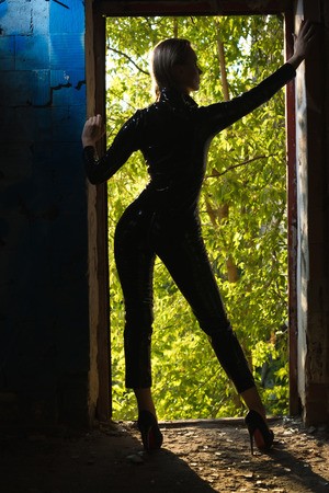 Sexy woman in a black latex costume in the style of an action movie Foto de archivo
