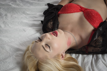Strangled beautiful woman in a red underwear lies on the bed. Simulation of the crime scene.   Stock Photo