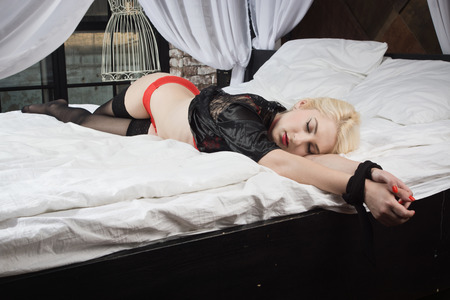 Strangled beautiful woman in a red underwear lies on the bed. Simulation of the crime scene.
