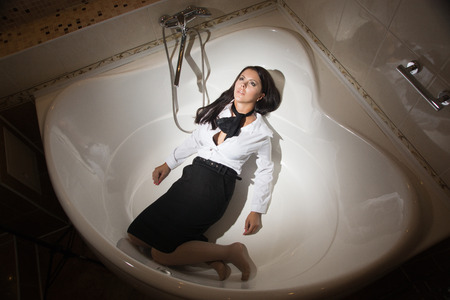 Strangled beautiful business woman in a bathroom. Simulation of the crime scene.