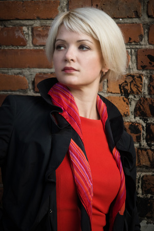 Noir film style woman in a black suit and red dress posing in a street