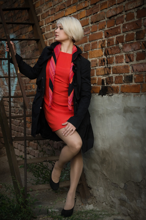 Noir film style woman in a black suit and red dress posing in a street  Stock Photo