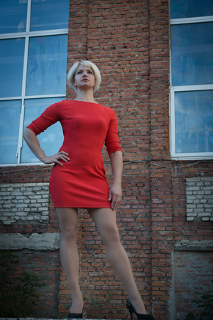 Noir film style woman in a red dress posing in a street