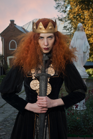 Medieval Queen with a sword in her hand on a church background