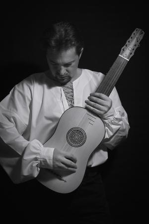 Man playing spanish renaissance instrument vihuela de mano over black  写真素材