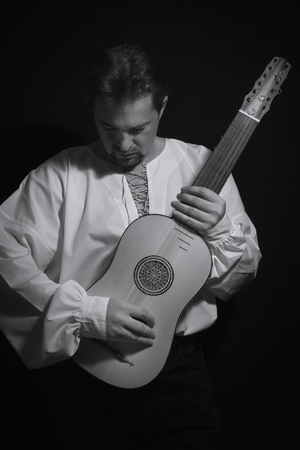 Man playing spanish renaissance instrument vihuela de mano over black  스톡 콘텐츠