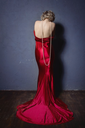 Beautiful woman in a long red dress in the vintage interior