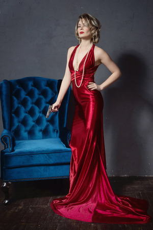 Noir film style woman in a red dress posing with a gun  Stock Photo