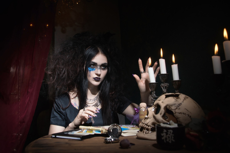 Evil witch conjures in a dark room Stock Photo