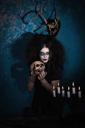 Evil witch with a skull in his hands