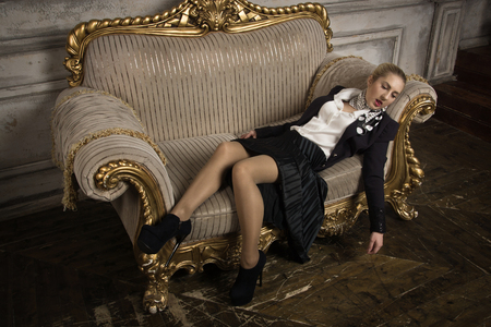 Crime scene (imitation). Strangled business woman lying on the couch
