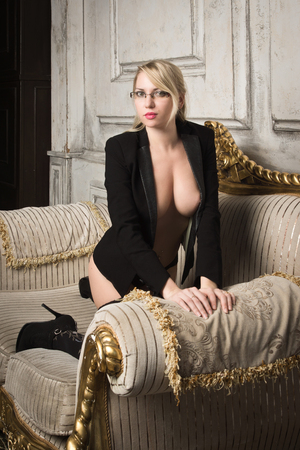 Sexy half-naked woman in glasses and business suit. Erotic concept