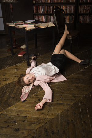 Crime scene (imitation). Strangled student in the classical library room Banque d'images