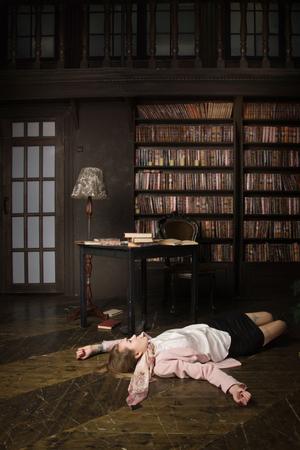 Crime scene (imitation). Strangled student in the classical library room Stock Photo