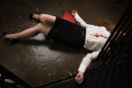 Crime scene. Business woman shot in the chest in old elevator Banque d'images