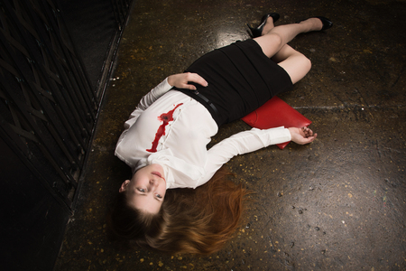 Crime scene. Business woman shot in the chest in old elevator Standard-Bild - 97419044