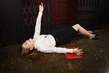 Crime scene. Business woman shot in the chest in old elevator Standard-Bild - 97419067