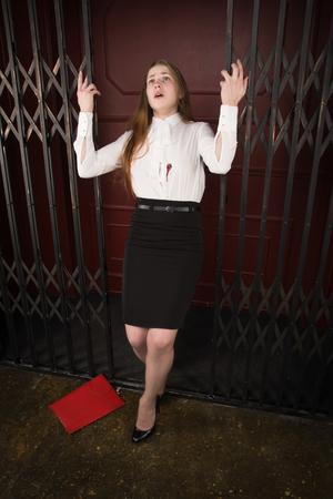 Crime scene. Business woman shot in the chest in old elevator Archivio Fotografico