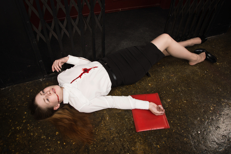 Crime scene. Business woman shot in the chest in old elevator 写真素材
