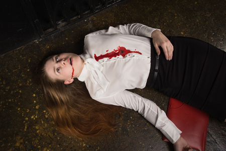 Crime scene. Business woman shot in the chest in old elevator