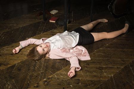 Crime scene (imitation). Strangled student in the classical library room Standard-Bild - 97764403