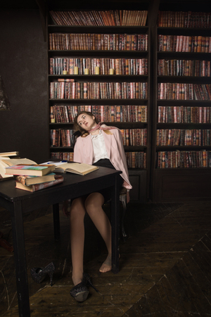 Crime scene (imitation). Strangled student in the classical library room Stock Photo - 97764406