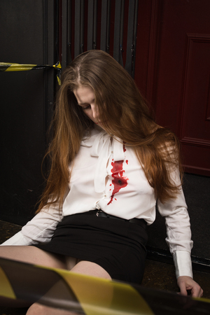 Crime scene. Business woman shot in the chest in old elevator Stock Photo