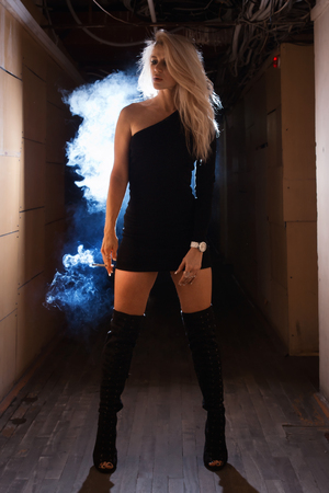 A pretty woman smokes in a dark room