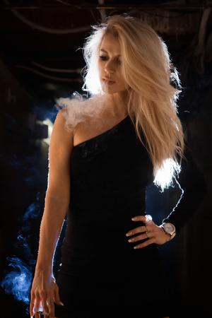 A pretty woman smokes in a dark room