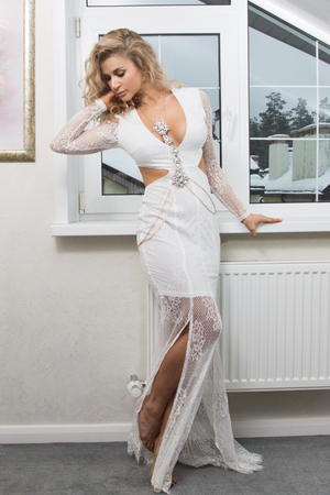 Beautiful woman in a long white dress in the vintage interior